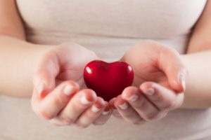 Heart in woman hands. Love giving, care, health, protection concept